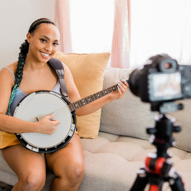young woman filming a video of herself playing a banjo