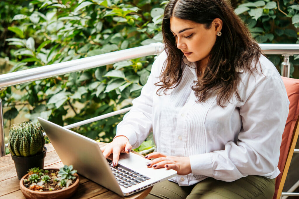 Latina woman in white shirt works on a laptop