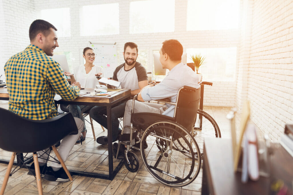 A man in a wheelchair communicates cheerfully with his coworkers during a business meeting.
