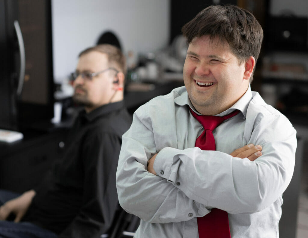 Man with Down Syndrome in a suit smiling during a meeting.